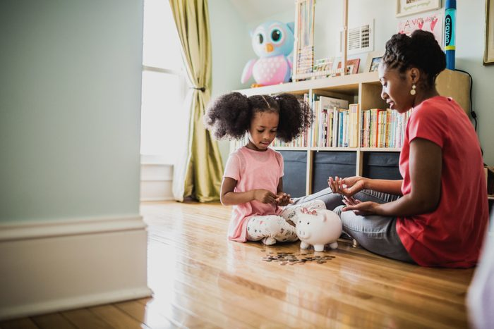 mother teaching daughter about money with piggy bank