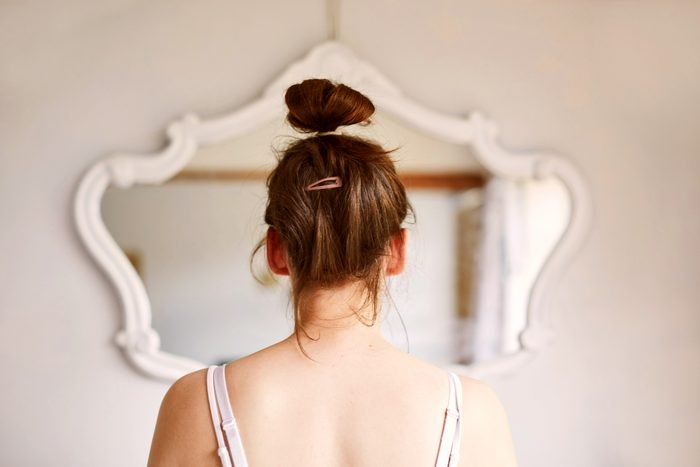 rear view of young woman looking in the mirror