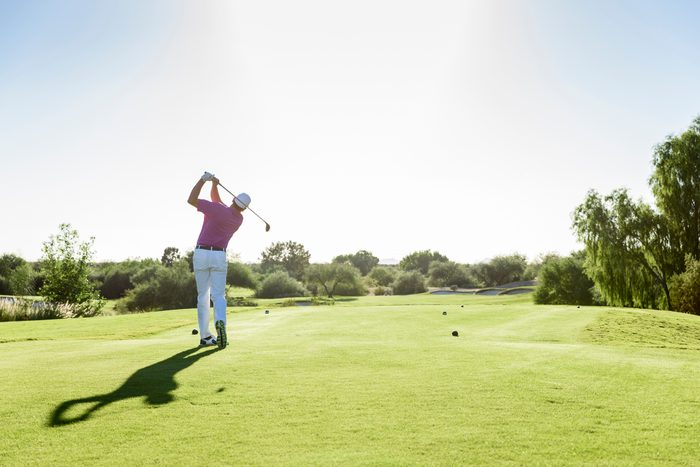 rear view of man playing golf