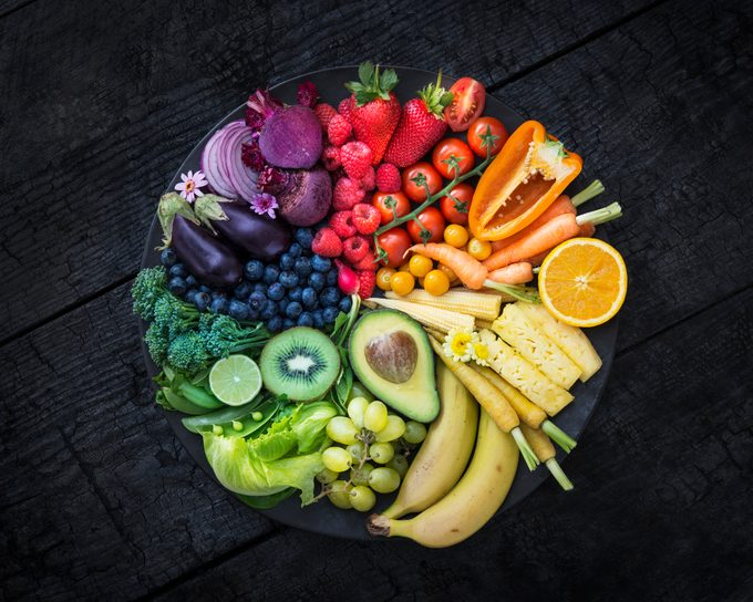 Multicoloured fruit and vegetables in a black bowl