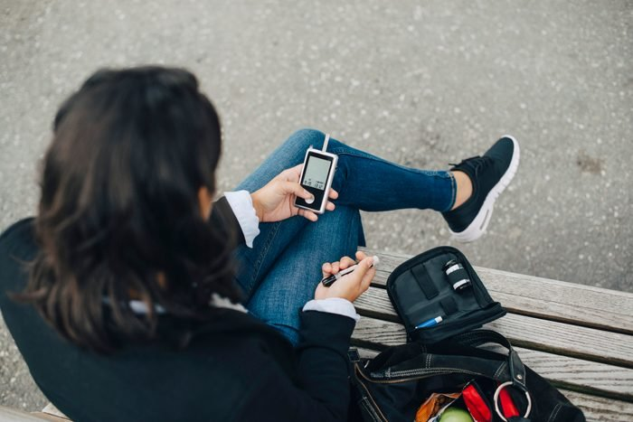 Woman checking blood sugar level while sitting on bench