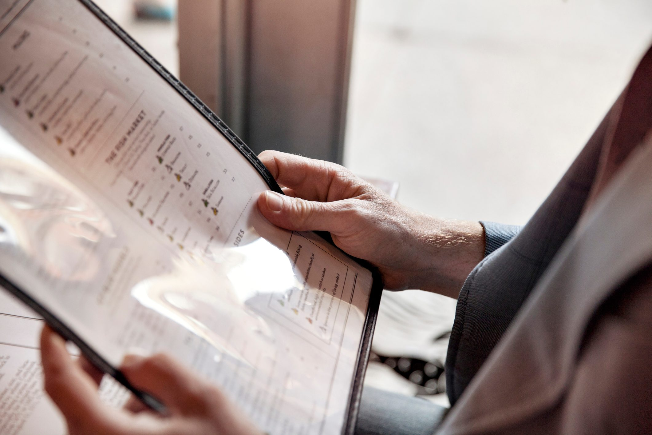 Cropped image of man holding menu while sitting in restaurant