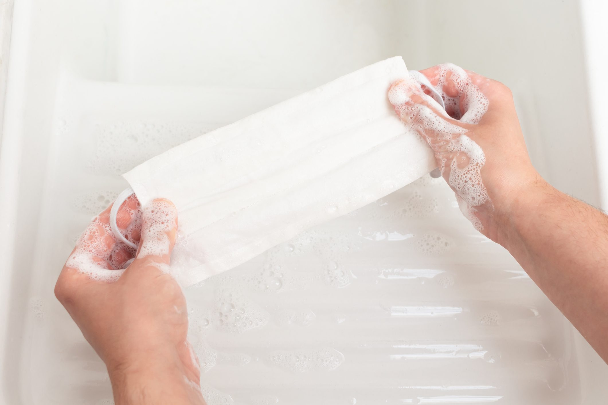 Woman's hands washing a reusable cloth face mask with soap in a white porcelain sink
