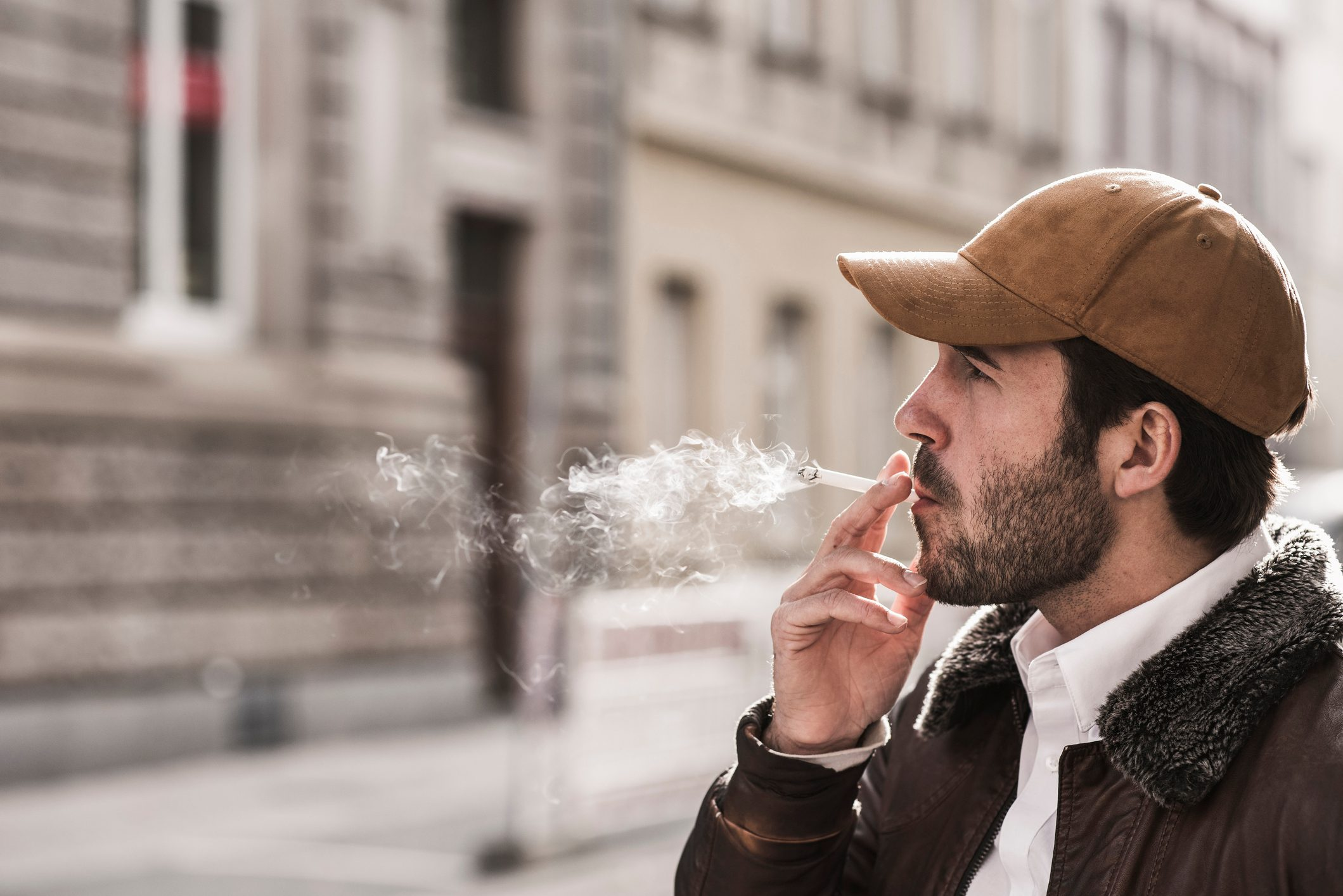 Portrait of young man with baseball cap smoking cigarette