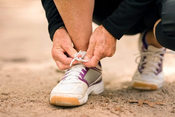 close up of person tying sneaker laces