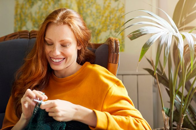 Woman knitting while sitting by plant on chair