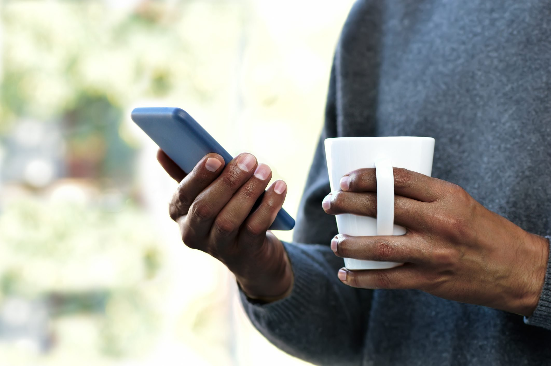 close up of person holding coffee mug and smartphone