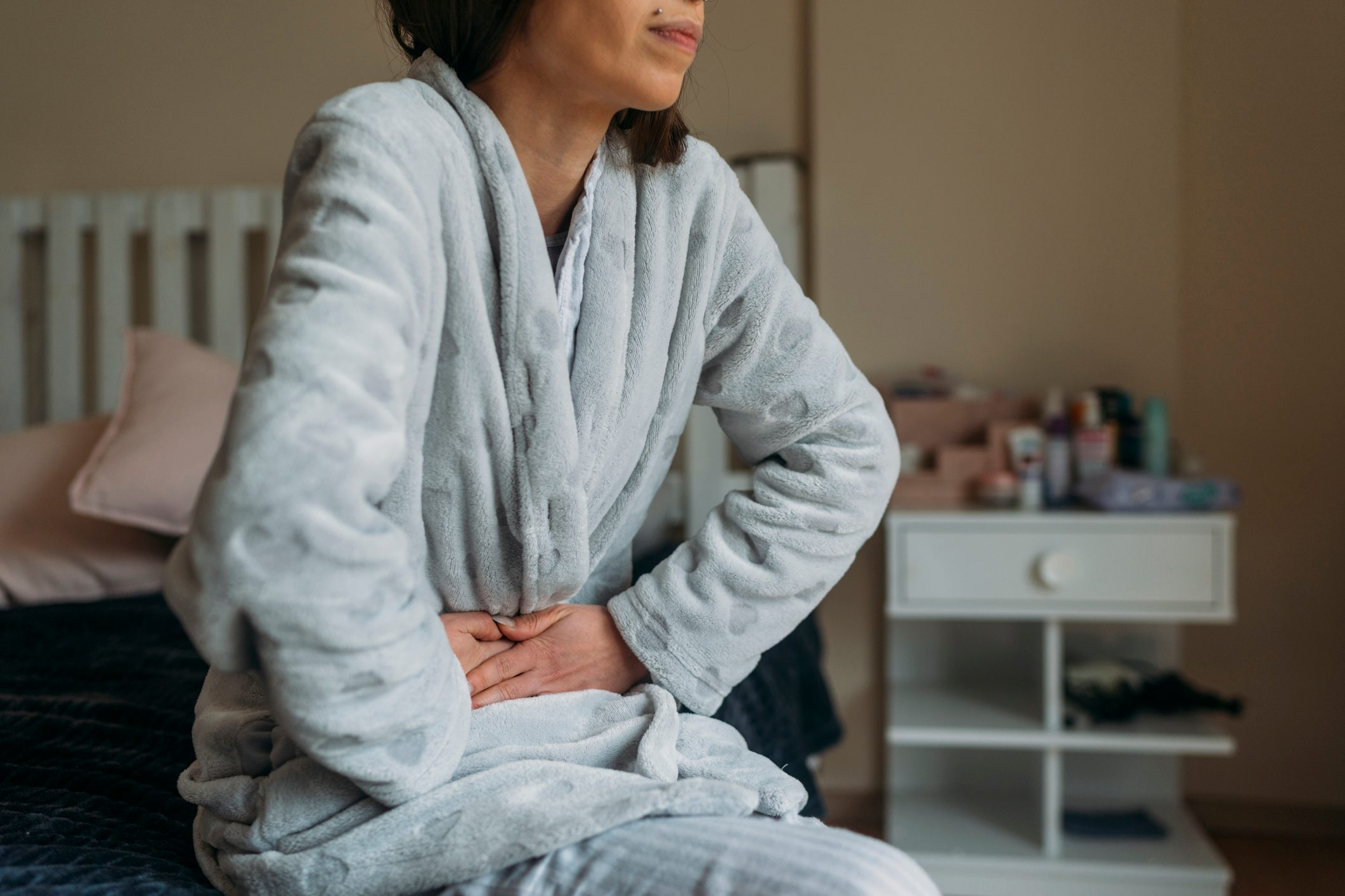 woman sitting on bed with Abdominal pain