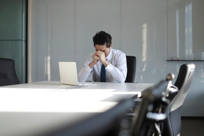 Stressed mature businessman with laptop