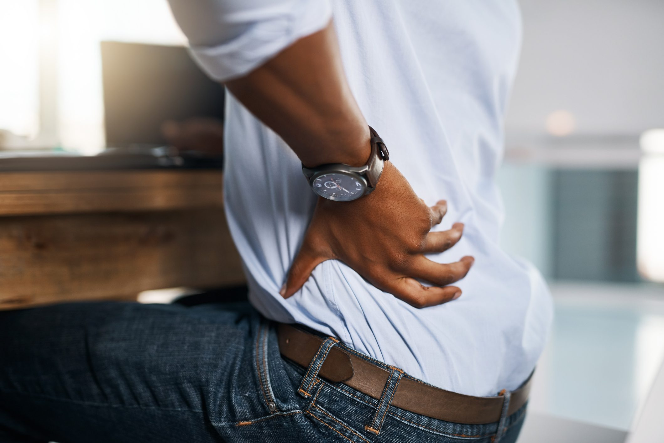 close up of man sitting at desk with lower back pain
