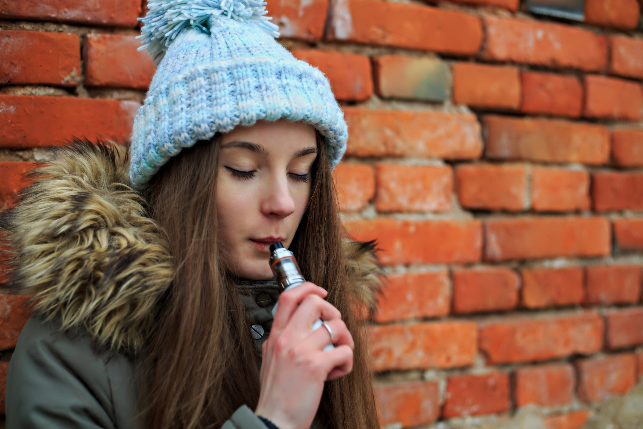 Vape teenager. Young pretty white girl in blue cap and green jacket smoking an electronic cigarette opposite brick wall on the street in the spring.