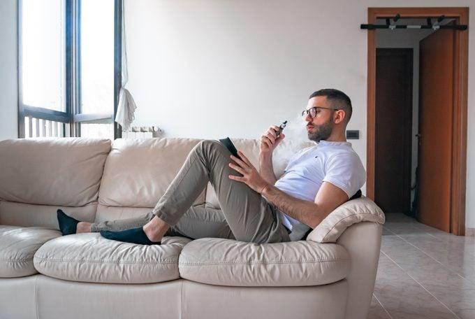 Man Smoking While Using Digital Tablet On Sofa At Home