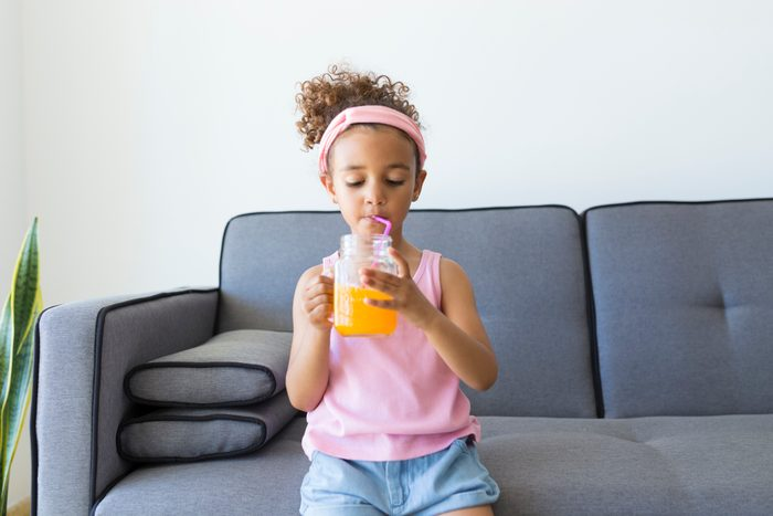 Girl sitting on couch at home having a drink