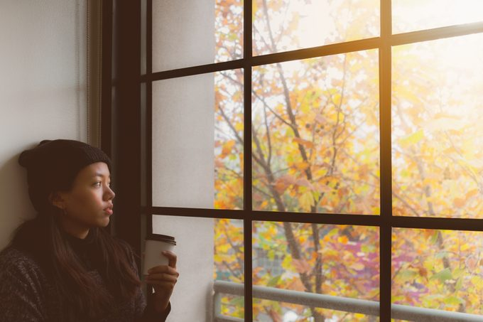 Woman Looking Through Window While Holding cup