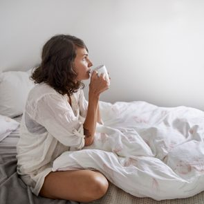 Relaxed young woman drinking coffee in bed