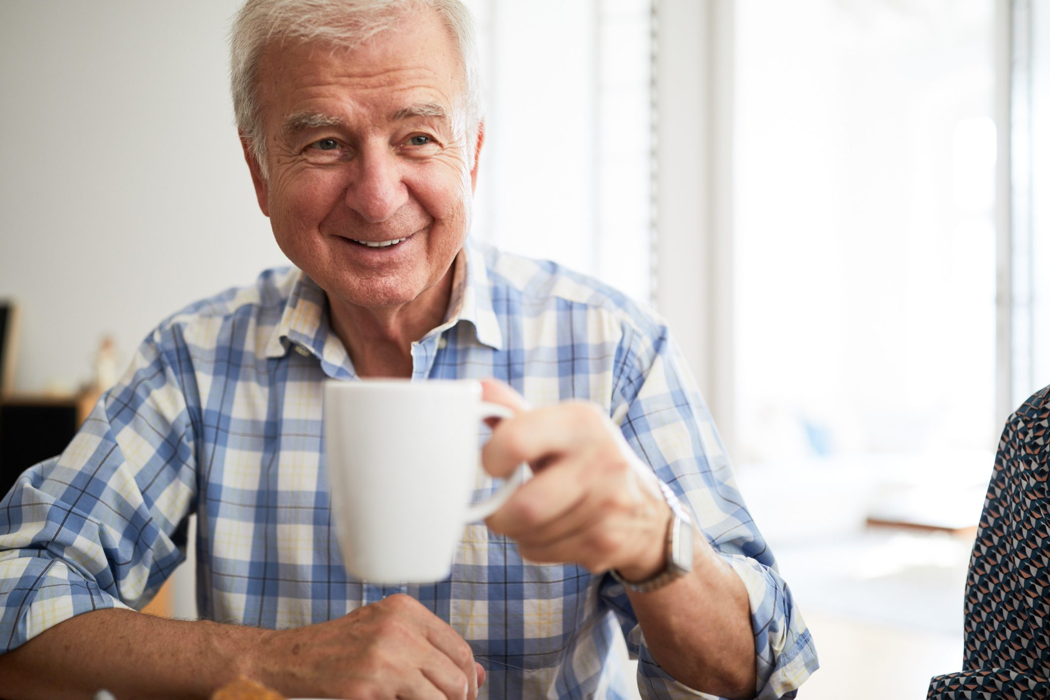 Senior man having tea at home