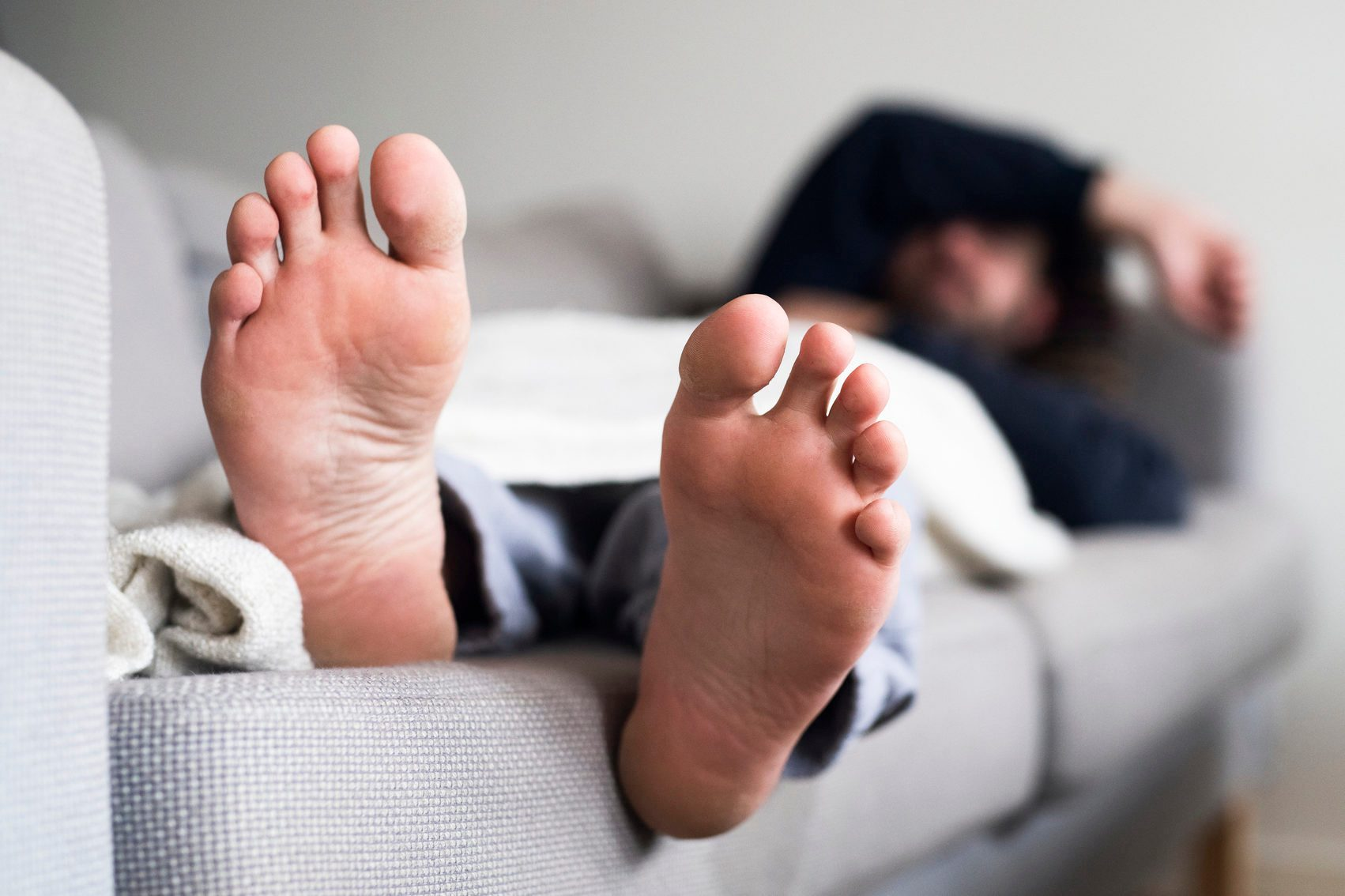 Man sleeping on sofa, close-up of feet