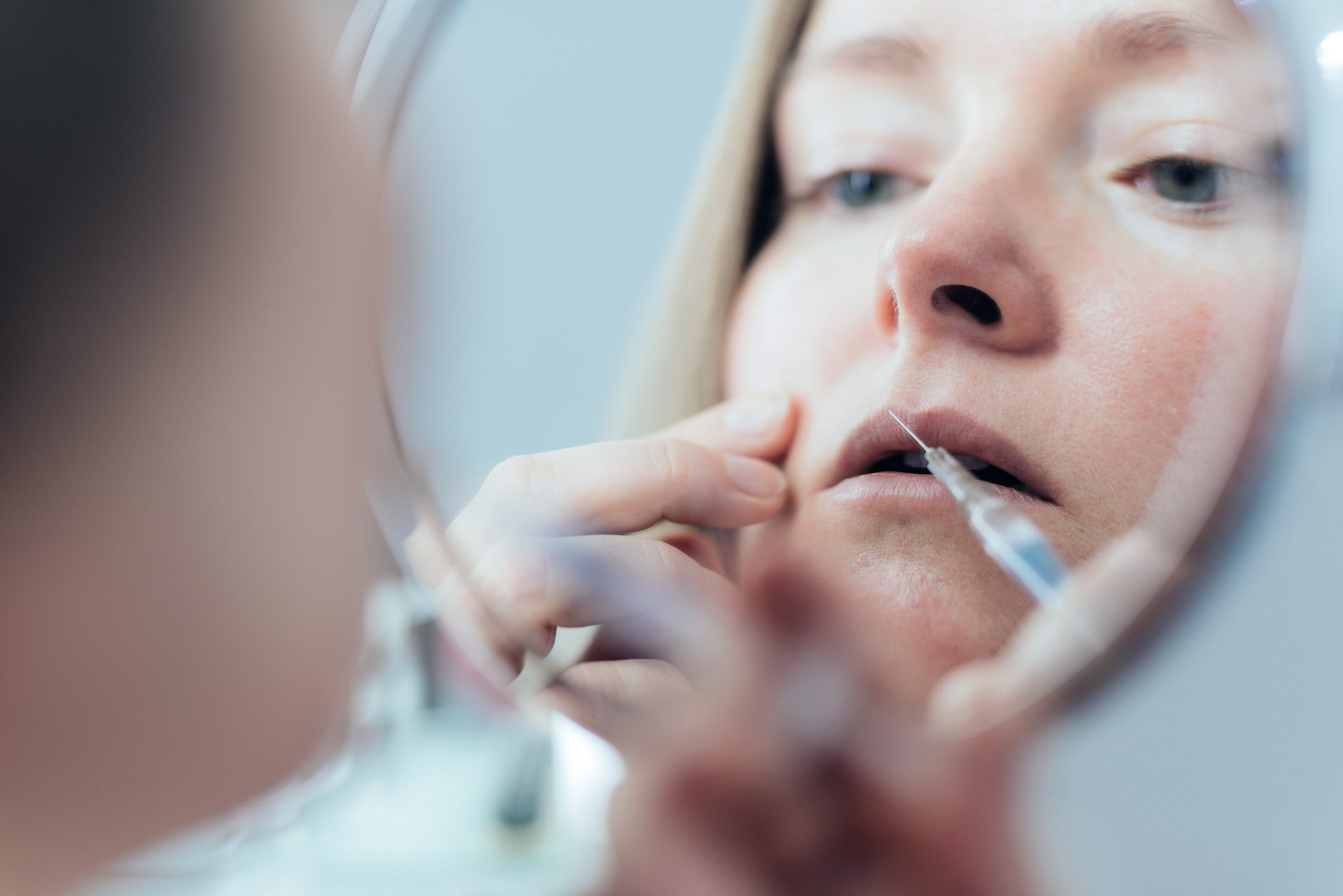 Woman doing botox injection in lips.