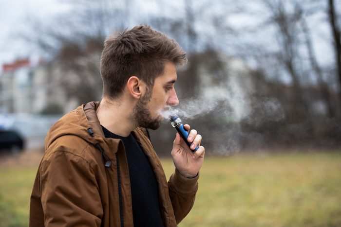 Young male worker smoking electronic cigarette
