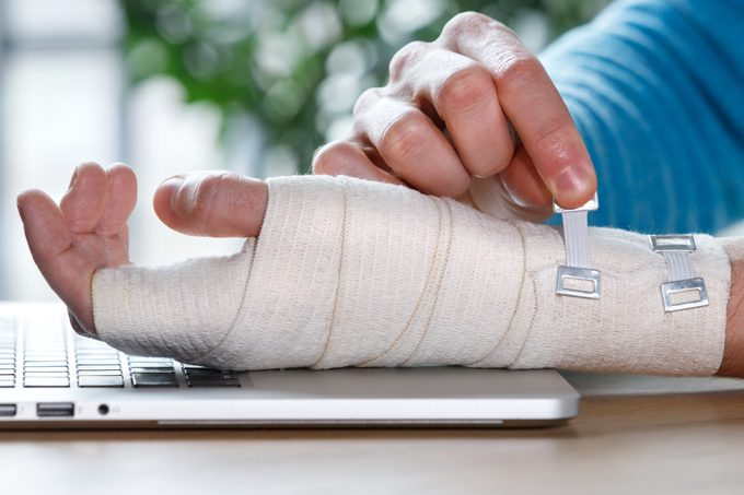 Close up of man arms wrapping his painful wrist with Flexible elastic supportive orthopedic bandage caused by prolonged work on laptop. Carpal tunnel syndrome, arthritis, arm sprain concept.