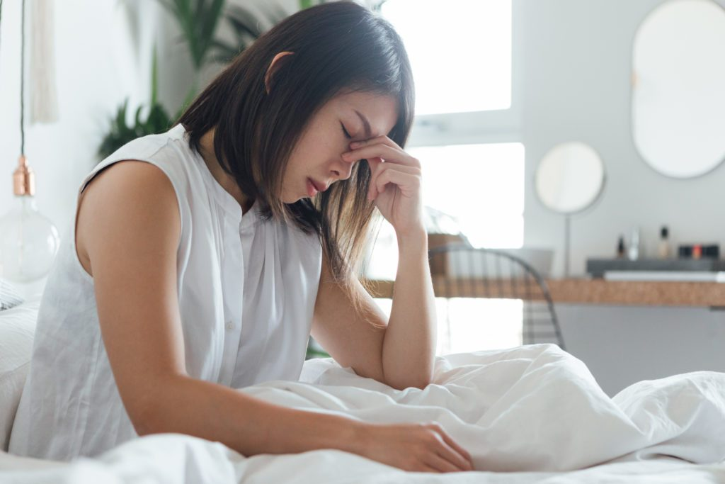 Young Woman Suffering Headache In Bed