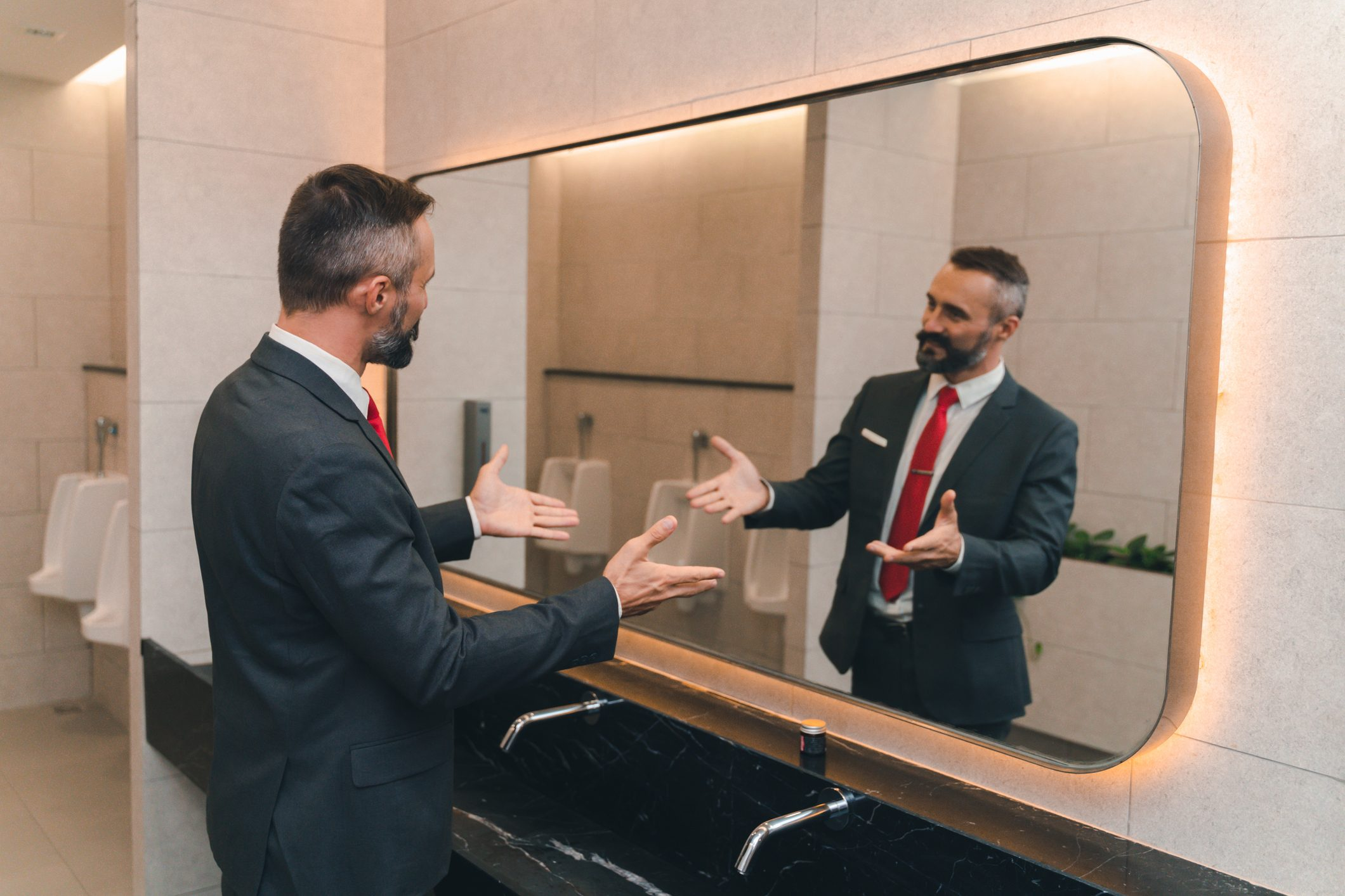 man business suit talking to himself in the bathroom mirror