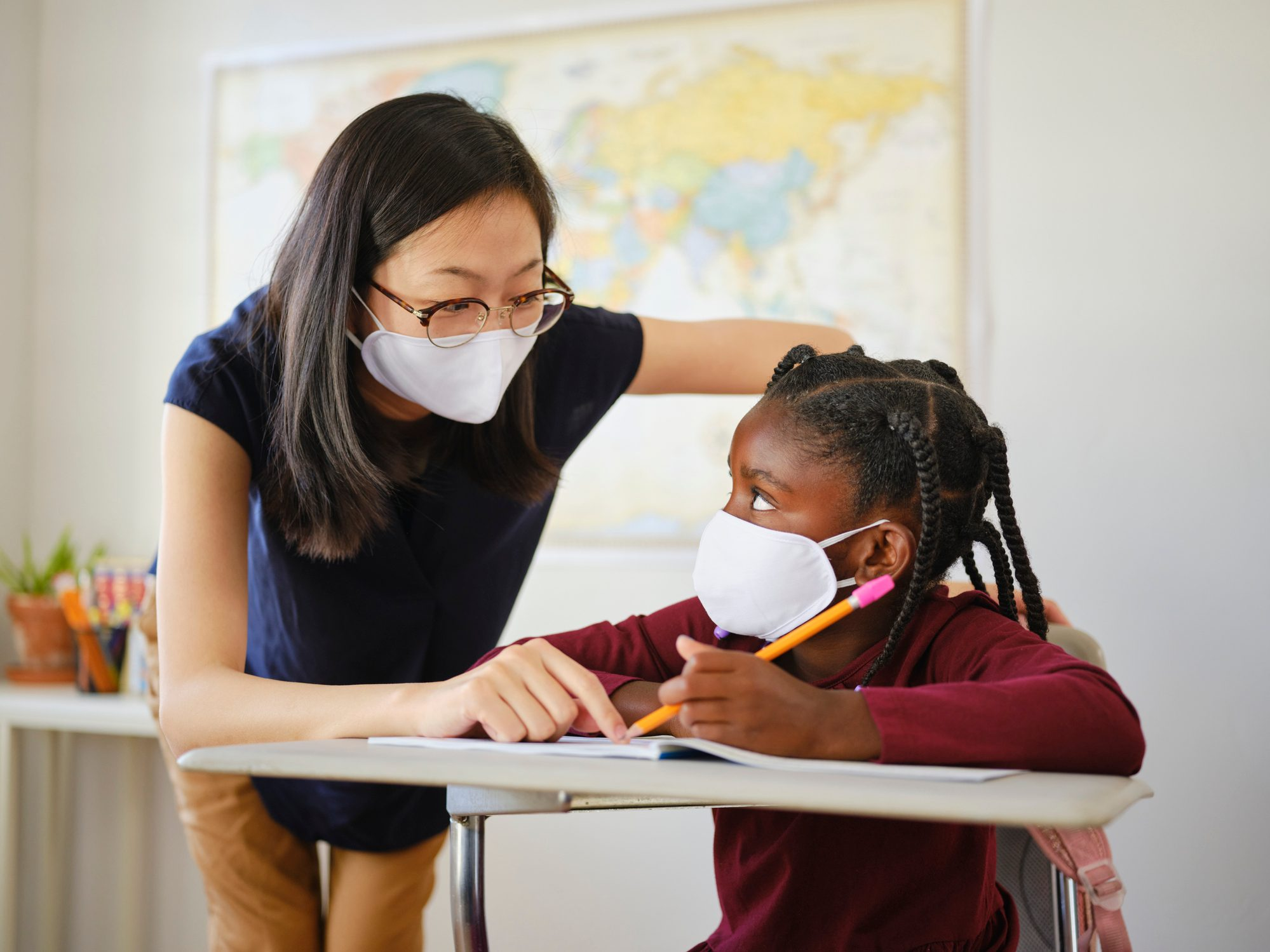 An Elementary School Student and Teacher in a Classroom