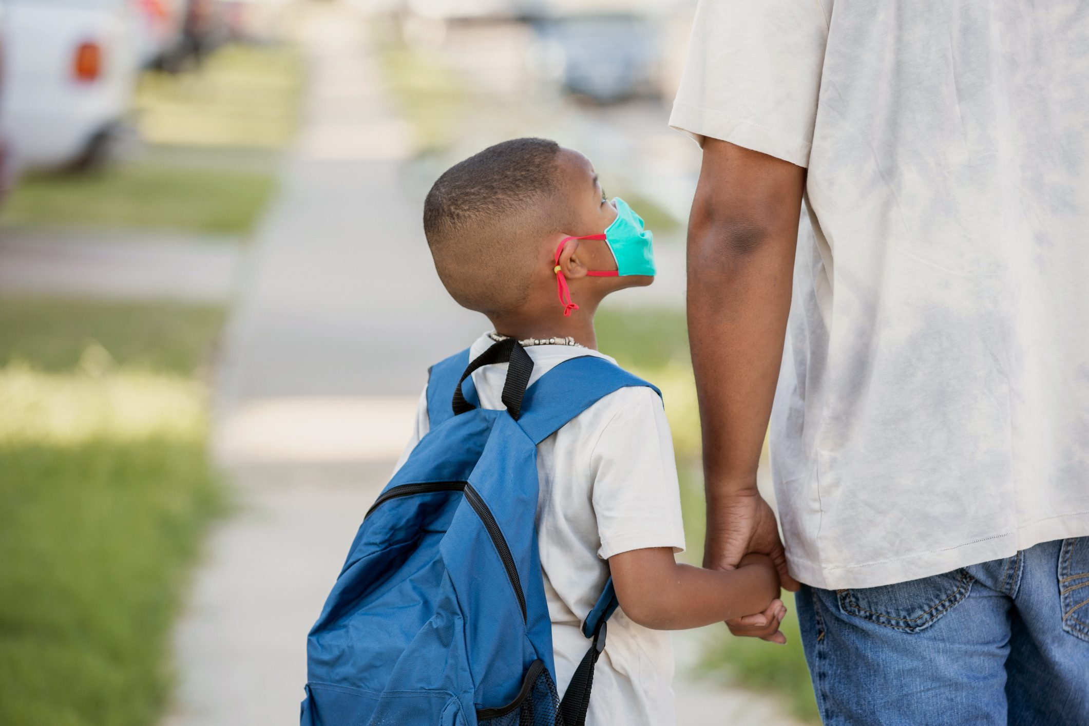 young boy holding his father's hand while walking to school with backpack and face mask