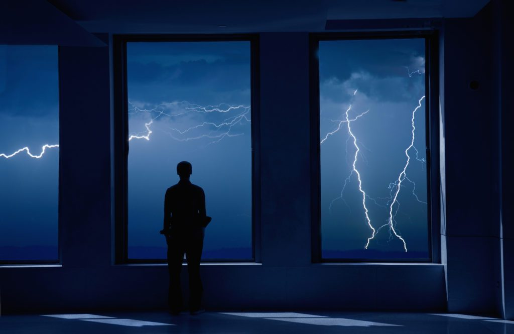 Man standing in window during storm.