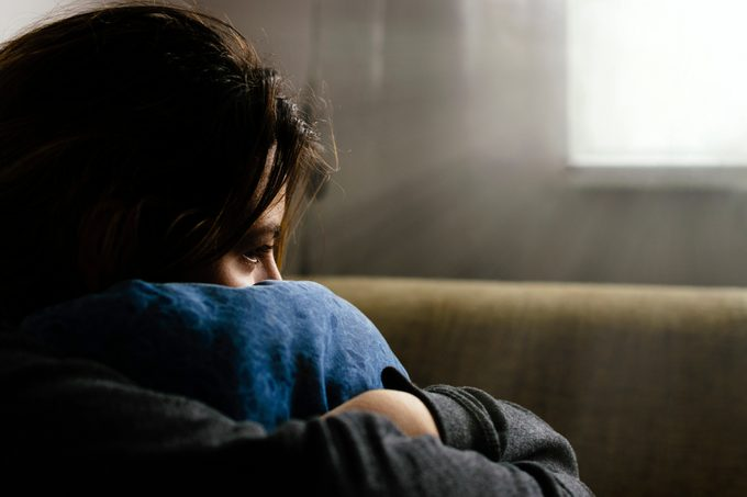 Close-Up Of Sad Woman Hugging Cushion While Sitting At Home