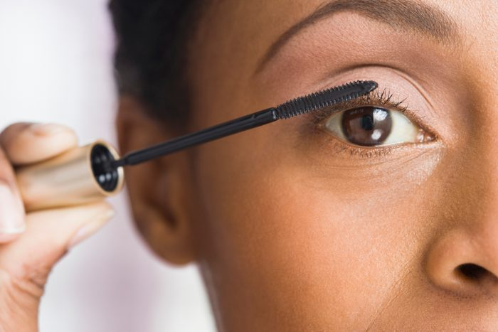 African American woman applying mascara