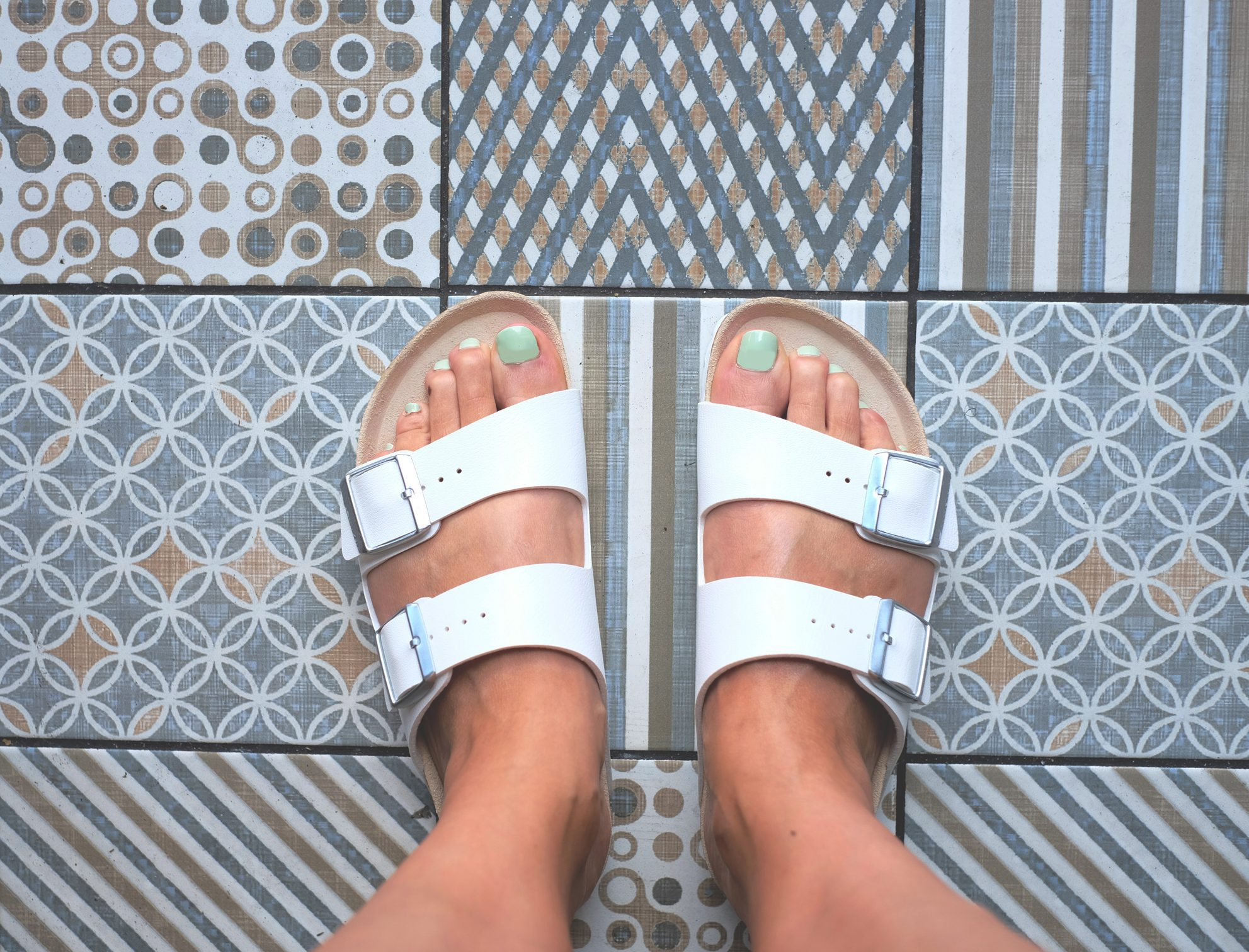Woman feet in a sandal with patterned background