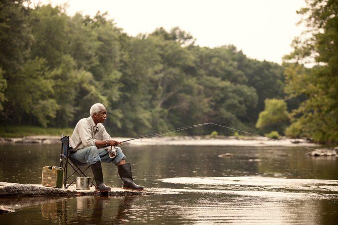 Man fishing while sitting on chair at lake