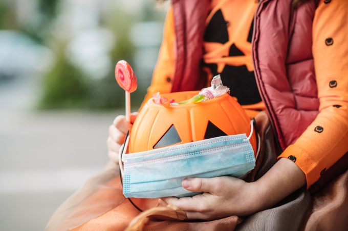Child's basket with sweets and protective face mask on Halloween in autumn
