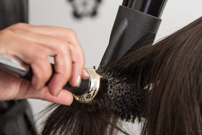 Close up of a hairdresser blow-drying woman's hair