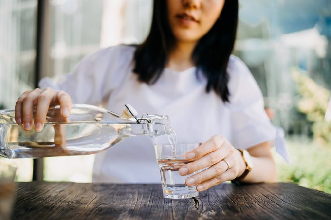 Woman pouring water from bottle into the glass