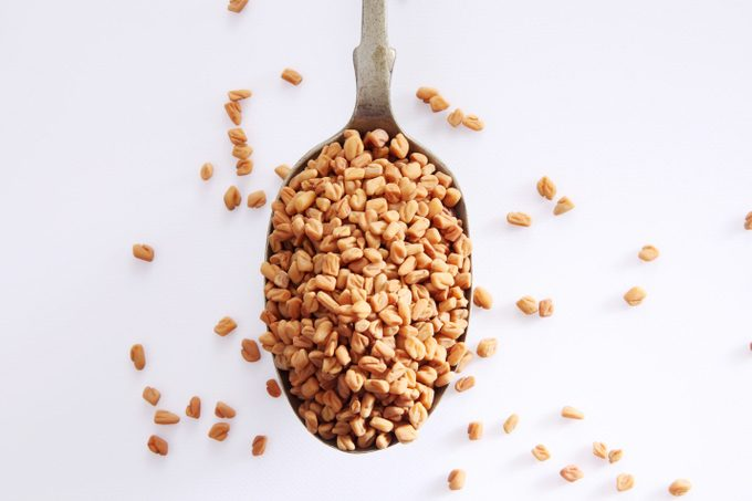 Fenugreek Seeds In Spoon Over White Background