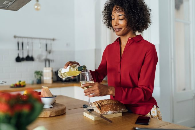 Woman standing in kitchen, pouring herself a glass of white wine