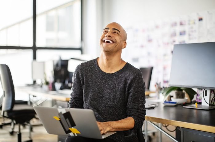 Businessman laughing with a laptop in office