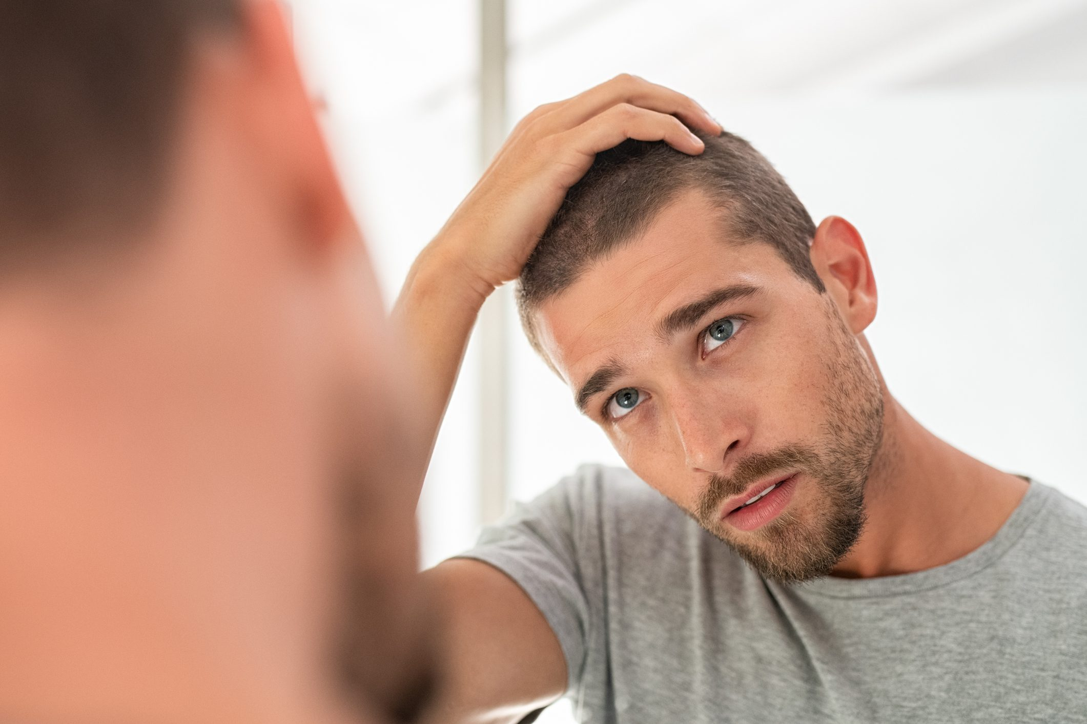 man checking hair in mirror