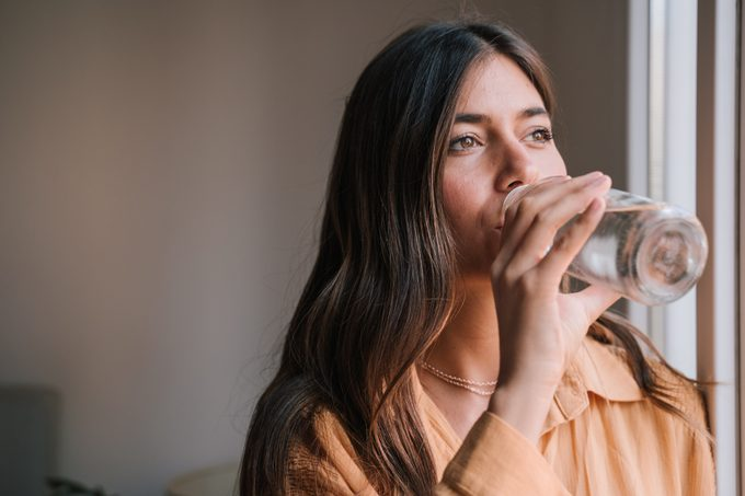 Young Woman Drinking Water In Glass Bottle By Window