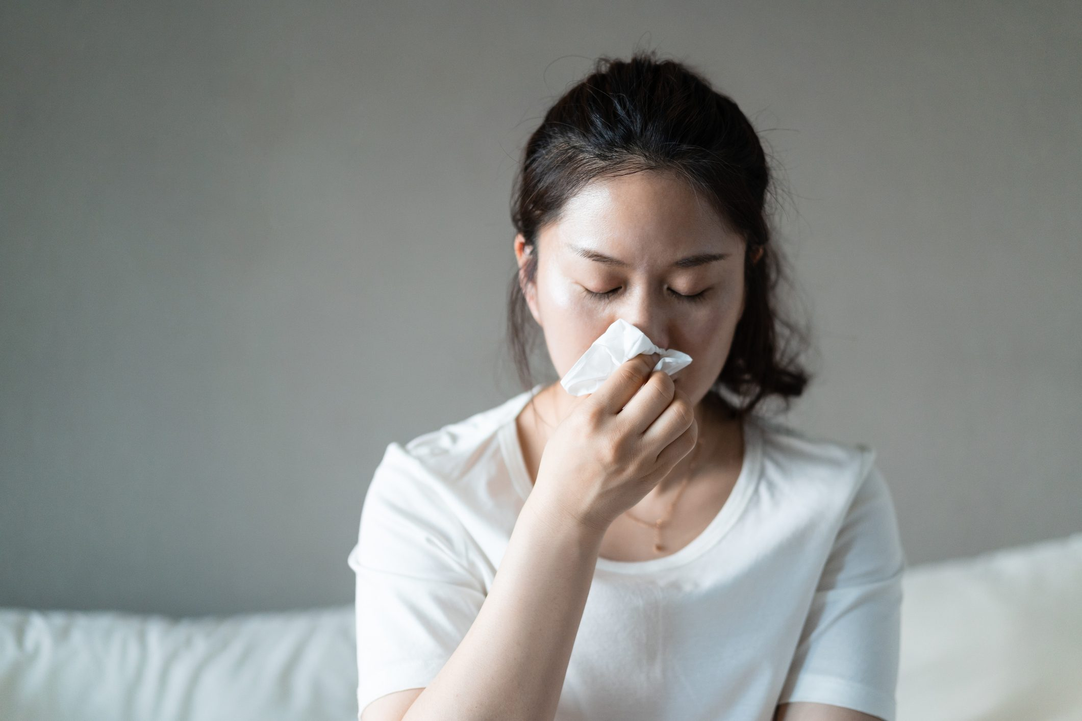 woman using a tissue to sneeze or blow her nose