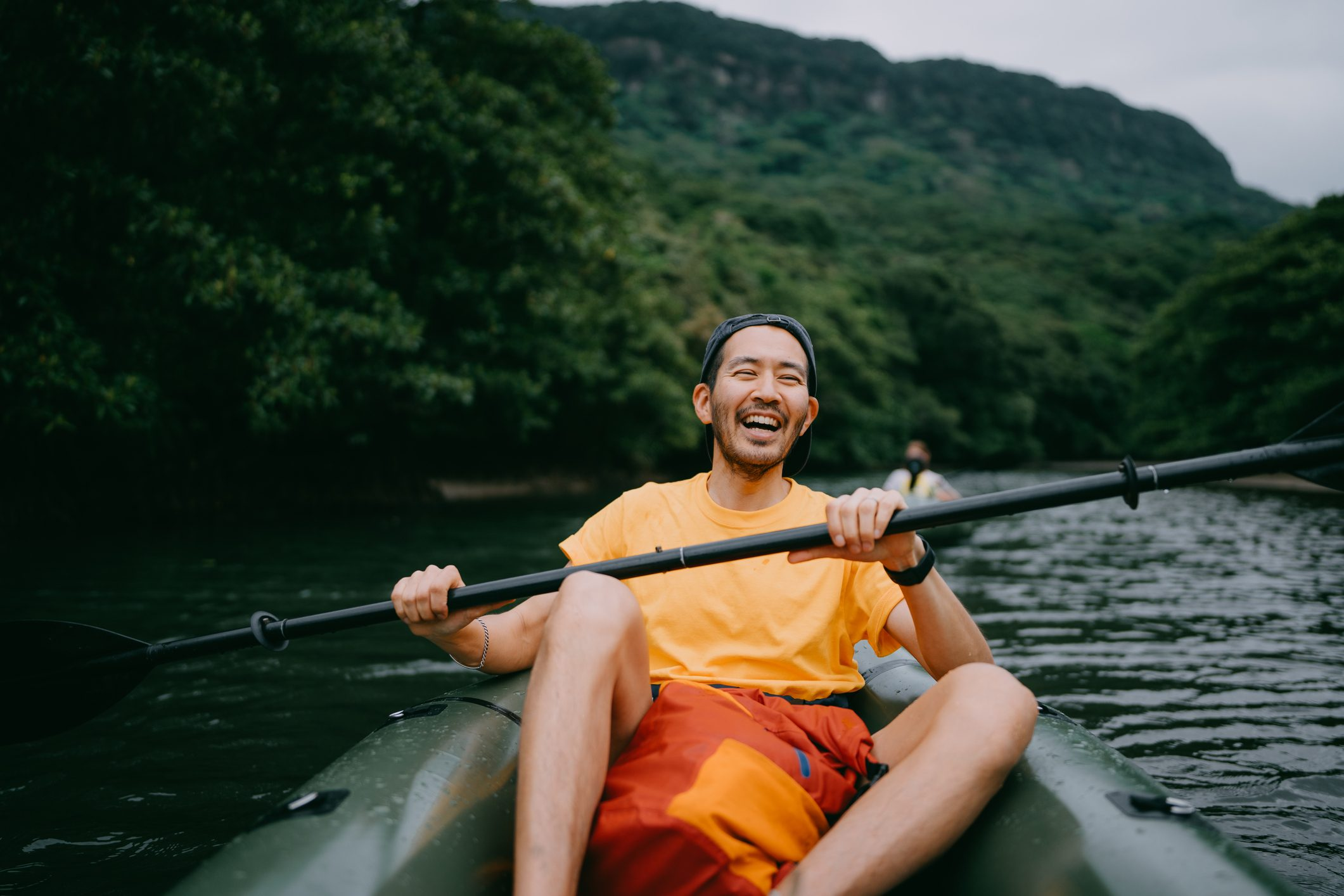 Man paddling kayak in mangrove river and laughing, Iriomote, Japan