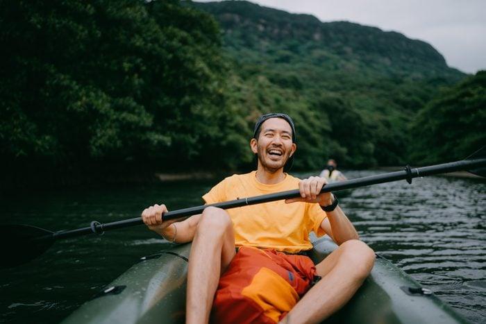 Man paddling kayak in mangrove river and laughing, Iriomote, Japan