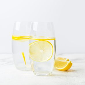two glasses of lemon water on white background