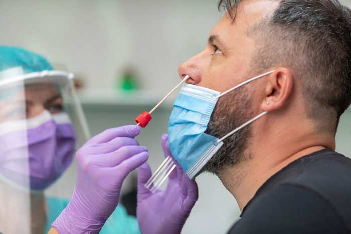 health care worker wearing protective gear taking nose swab test