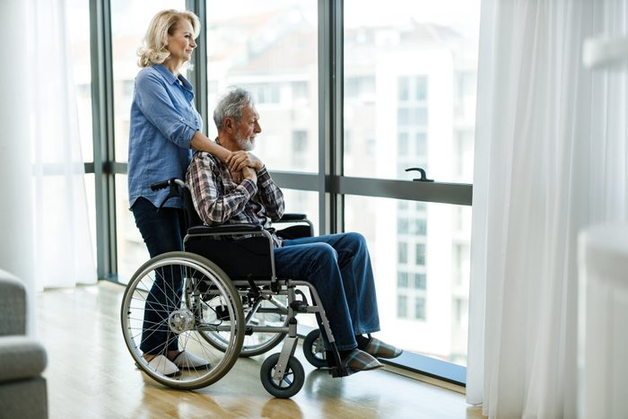 Mature woman with man in wheelchair looking through window.
