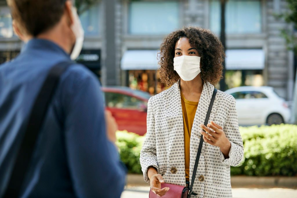 Businesswoman Wearing Protective Face Mask Talking To Male Coworker During COVID-19 Pandemic In City