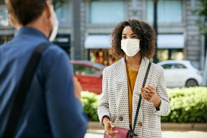 woman Wearing Face Mask Talking To man During COVID-19 Pandemic