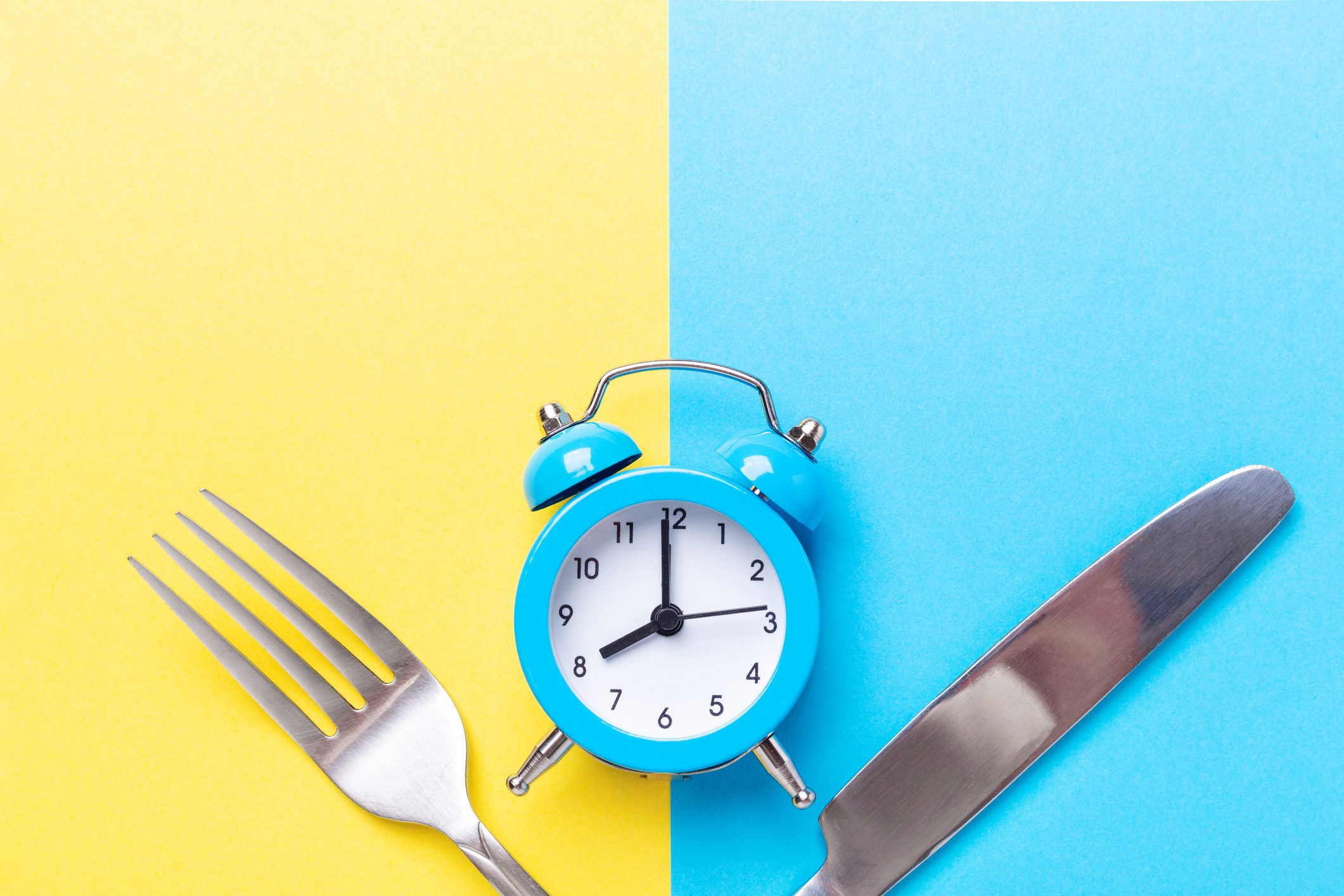Blue alarm clock, fork, knife on colored paper background. Intermittent fasting concept